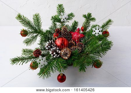 Christmas table centerpiece with red balls and rustic ornaments. Christmas decoration with fir branches and red baubles. Christmas background with greenery in wicker basket.