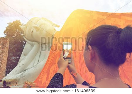 closeup of woman's hands holding mobile phone and taking photo of buddha in Thailand