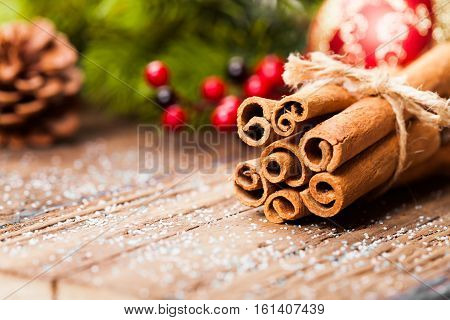 cinnamon and christmas decoration on wooden background