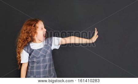 School girl showing disgusted emotion facial expression and hand raise to stop or protect.