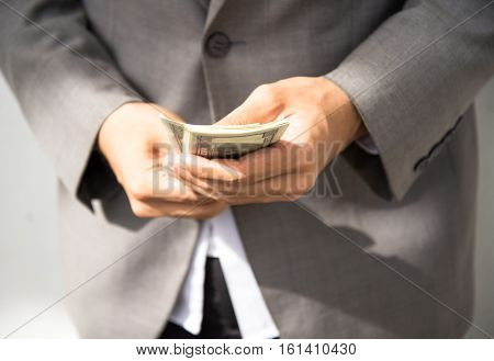 Business executive in formal suit giving money as a bribe select focus