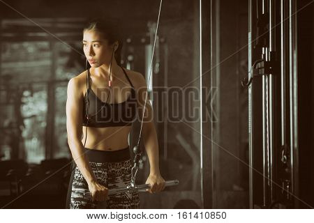 Toned picture, Fitness woman, Asian woman flexing arm muscles on cable machine in gym.