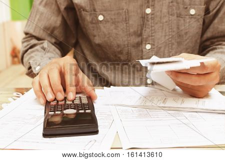Asian young man sitting on home office using calculator and calculating bills.