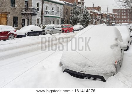 Montreal CA - 12 December 2016: Cars covered in snow during snowstorm