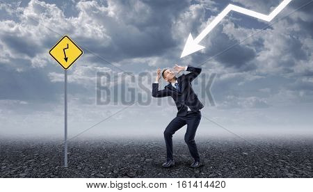 Businessman standing on a rocky ground frightened by a lightning, near yellow road sign with the same arrow painted on it. Business crisis. Temporary difficulties. Emotional pressure.