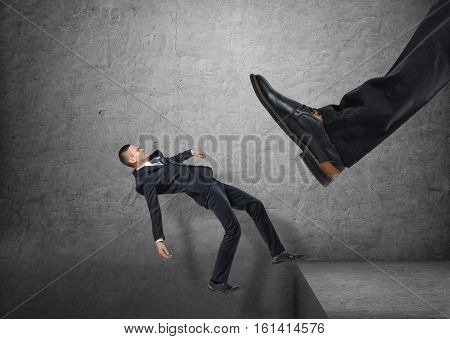 A giant foot in a black shoe kicking a little businessmen off the edge, and he is falling down, on the concrete gray background. Major defeat. Bankruptcy and insolvency. Failing business.
