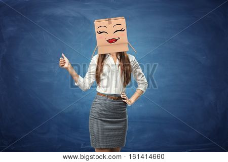 Young beautiful woman showing her thumb up and wearing cardboard box with drawn smiley face with red full lips. Anonymous person. Support and approval. Good idea. Success in business.