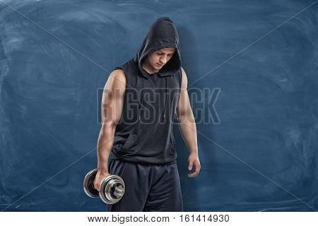 Portrait of a young handsome man in a black outfit standing and holding a silver dumbbell in his hand during training on blue chalkboard background. Sport and healthy lifestyle. Keep fit. Athletic body. Exercises and warming up.