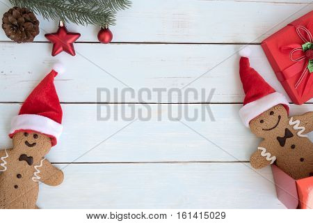 Christmas background with santa claus gingerbread man cookies with open gift box and fir branch decoration on vintage wooden table flat lay with copy space