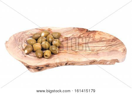 Green colossal olives hand stuffed with garlic gloves in olive wood cutting board isolated on white background