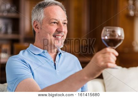 Smiling mature man drinking a glass of wine at home