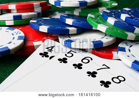 A low angle image of poker chips and cards on a poker table.