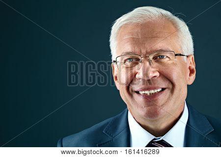 Portrait of a smiling senior businessman looking away, studio portrait