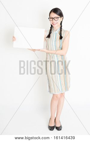 Portrait of young Asian woman in traditional qipao dress hand holding white blank paper card, celebrating Chinese Lunar New Year or spring festival, full body standing on plain background.