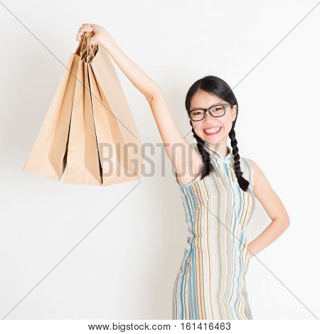 Portrait of young Asian female in traditional qipao dress shopping, hand holding paper bag, celebrating Chinese Lunar New Year or spring festival, standing on plain background.