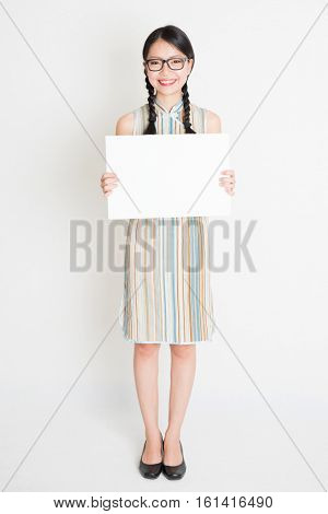 Portrait of young Asian woman in traditional qipao dress hand holding a white blank paper card, celebrating Chinese Lunar New Year or spring festival, full body standing on plain background.