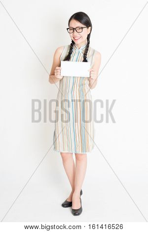 Portrait of young Asian female in traditional qipao dress hand holding white blank paper card, celebrating Chinese Lunar New Year or spring festival, full body standing on plain background.