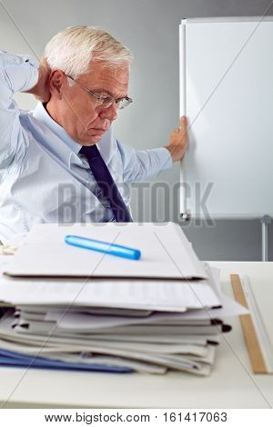 Senior man sitting with pensive expression at paper pile
