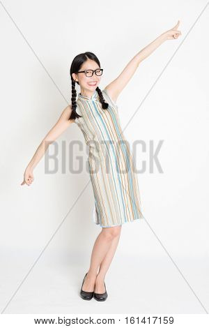 Portrait of young Asian girl in traditional qipao dress finger pointing at something, full length standing on plain background.