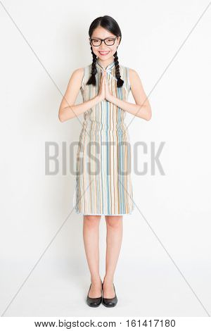 Portrait of young Asian girl in traditional qipao dress in greeting pose, full length standing on plain background.