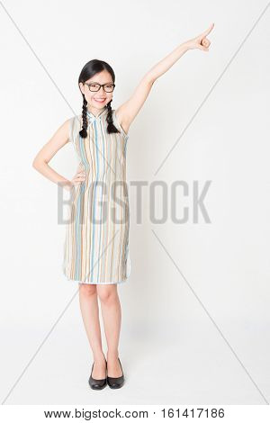 Portrait of young Asian girl in traditional qipao dress finger pointing away, full length standing on plain background.