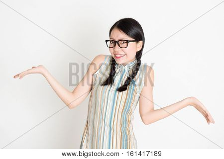 Portrait of young Asian girl in traditional qipao dress unsure and shrugging shoulder, standing on plain background.