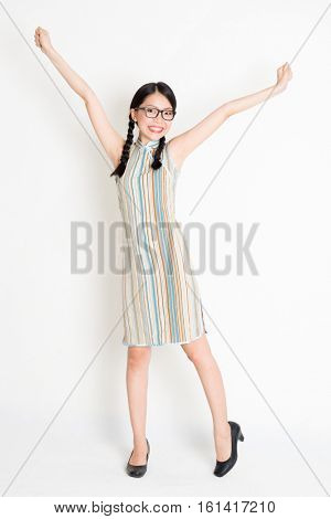 Portrait of excited young Asian girl in traditional qipao dress arms raised, full length standing on plain background.