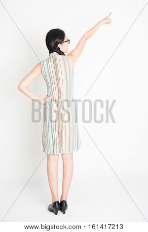 Rear view of young Asian girl in traditional qipao dress hand pointing away, full length standing on plain background.
