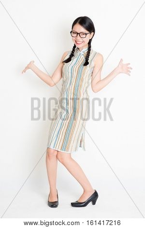Portrait of excited young Asian girl in traditional qipao dress, full length standing on plain background.