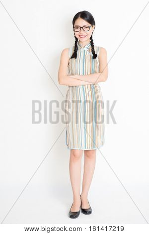 Portrait of young Asian girl in traditional qipao dress smiling, full length standing on plain background.