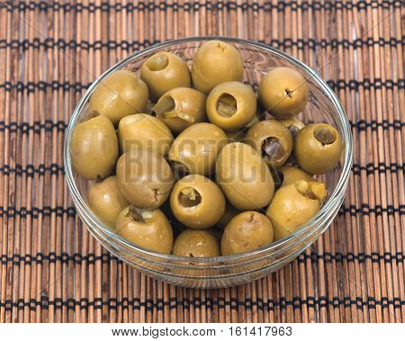 Green colossal olives hand stuffed with jalapeno peppers in bowl on bamboo placemat