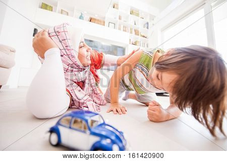 Happy Muslim Middle Eastern mother with son at new modern home family at new modern home playing car toy