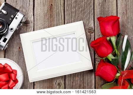 Valentines day roses, photo frame, retro camera and gift box over wooden background