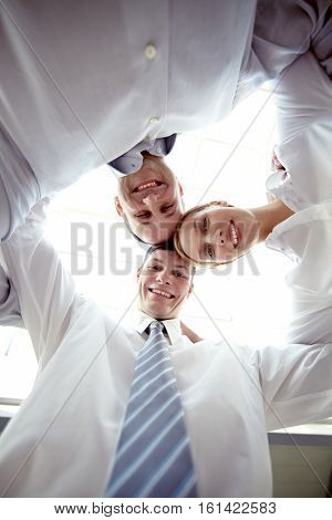 Low angle view of three colleagues embracing, looking at camera and smiling