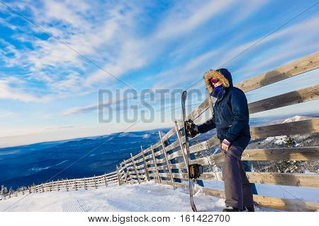 Successful young man snowboarding in the mountains Sheregesh. Snowboarder resting on mountain top. Caucasian snowboarder on a background of blue sky . Stylish caucasian snowboarder.  ski resort