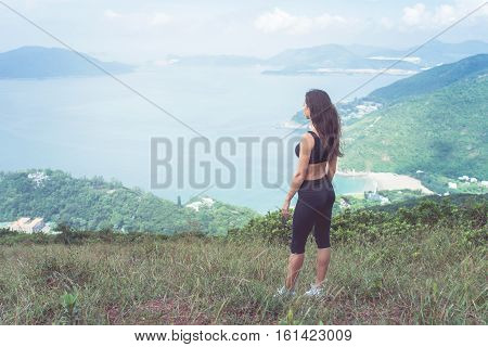 Sporty young woman standing on hill admiring the view of sea and green mountains in sunlight.