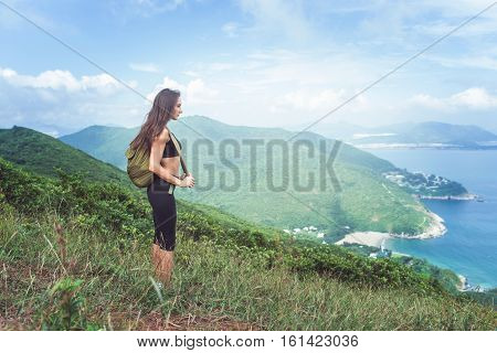 Backpack female traveler standing on hill looking at sea and mountains. Trail runner taking a break and enjoying view of nature.