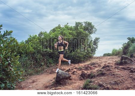 Young sportswoman cross country running on dirty rocky footpath in mountains in summer. Fit girl jogging outdoors in countryside