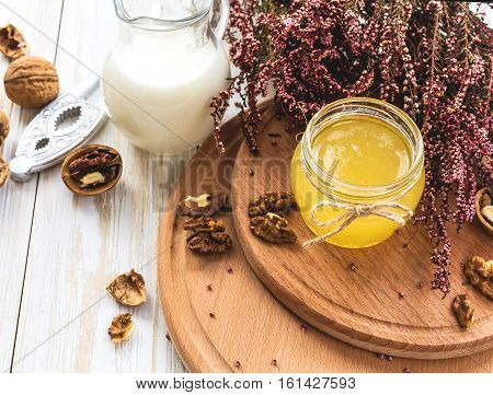 Milk, Heather Flowers, Walnuts And Honey. Wooden Table.