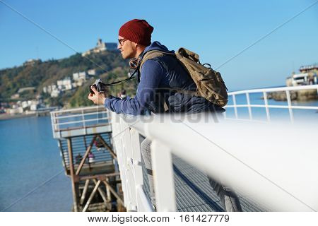 Man taking pictures from footbridge by the sea