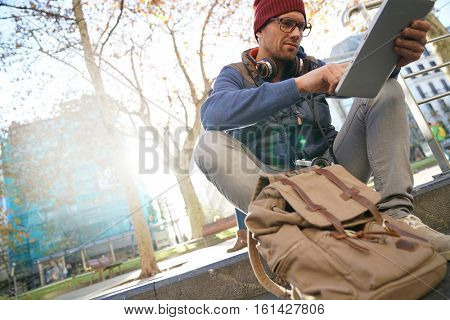 Hipster guy in the street websurfing on tablet