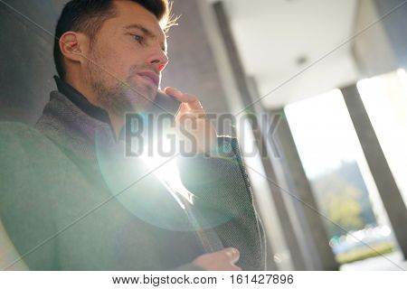 Businessman leaning on wall talking on phone