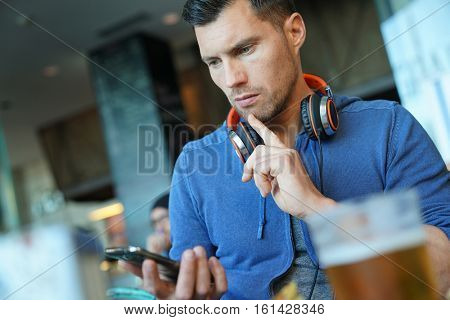 Man relaxing in restaurant, using smartphone