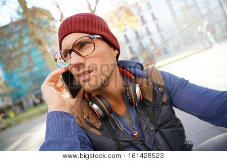 Hipster guy in town talking on phone