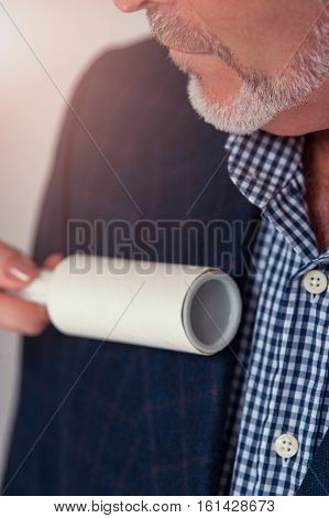 Cropped shot of senior bearded businessman in smart casual dress. Female hand cleaning suit with sticky brush.