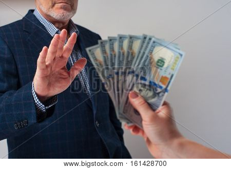 Bribery and corruption concept. Cropped shot of senior businessman refusing to take bribe from partner.