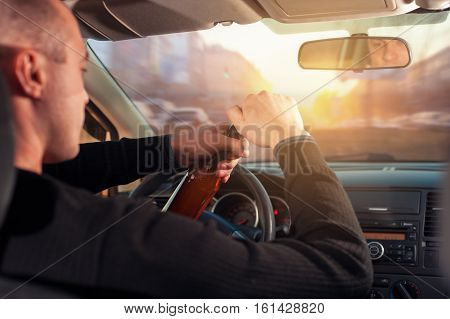 Cropped shot of young Man drinking alcohol while driving a car. Transportation and vehicle safety.
