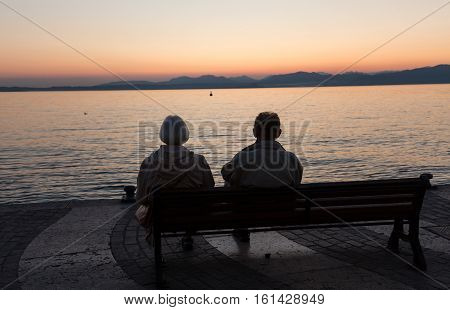 Aged couple sitting on a bench and looking at sunset at Garda Lake Italy