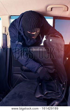 Thief in robbery mask breaking into a car and stealing handbag.