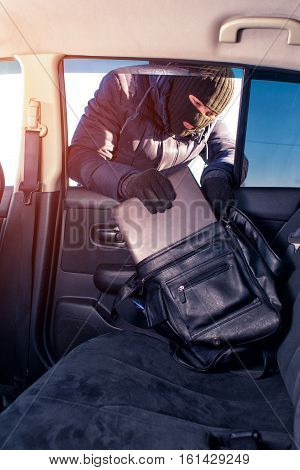 Thief in black robbery mask stealing laptop from car